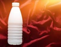 Garrafa plástica branca do iogurte em uma toalha de mesa de seda vermelha, vista superior imagem de stock royalty free