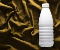 Garrafa plástica branca do iogurte na toalha de mesa de seda amarela, vista superior fotografia de stock