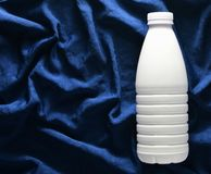 Garrafa plástica branca do iogurte na toalha de mesa de seda azul, vista superior fotos de stock