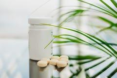 Garrafa plástica com os comprimidos claros dispersados no vidro imagens de stock