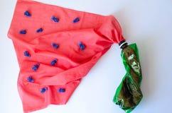 Garrafa plástica com um pano coral em que as flores azuis fotos de stock royalty free