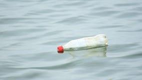 Garrafa plástica do refresco do casco ao flutuar na água do oceano em Singapura, Singapura, o 16 de dezembro de 2018 filme