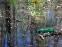 Garrafa plástica em uma lagoa fotos de stock royalty free