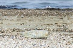Garrafa plástica na praia imagem de stock royalty free