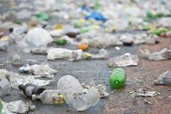 Garrafa plástica na terra e em mais lixo Fotografia de Stock