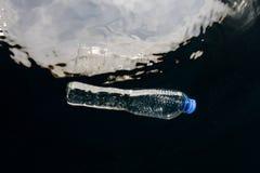 Garrafa plástica que deriva no oceano foto de stock