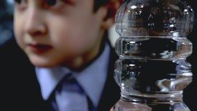 Garrafa plástica transparente clara com fim da água acima e uma estudante borrada que senta-se pela tabela, mastigando no fundo filme