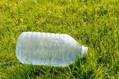 Garrafa pl?stica vazia em um gramado verde Conceito: polui??o ambiental fotografia de stock royalty free