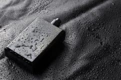 Garrafa preta do parfume com o tampão aberto no fundo preto das gotas da água Closeu disparou imagens de stock royalty free