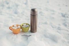Garrafa térmica e marshmallow de prata no copo na neve Fotografia de Stock Royalty Free