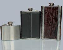 Garrafa três lisa para o álcool isolado em um fundo cinzento Imagem de Stock