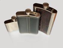 Garrafa três lisa para o álcool isolado em um fundo cinzento Fotografia de Stock Royalty Free