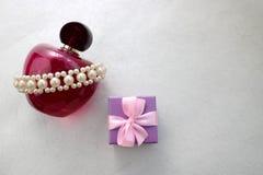 Garrafa transparente de vidro bonita cor-de-rosa do perfume fêmea decorada com as pérolas preciosas brancas e caixa de presente e Fotografia de Stock