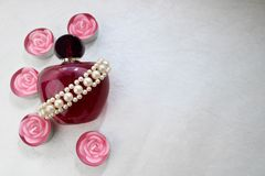 Garrafa transparente de vidro bonita roxa do perfume fêmea decorada com as pérolas monótonos brancas e velas cor-de-rosa da paraf Fotos de Stock