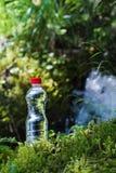 A garrafa transparente do plástico A da agua potável com uma tampa vermelha está na grama e no musgo no fundo de um áspero Foto de Stock