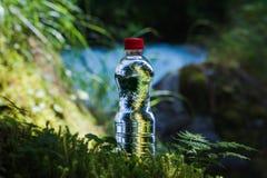 A garrafa transparente do plástico A da agua potável com uma tampa vermelha está na grama e no musgo no fundo de um áspero Imagem de Stock