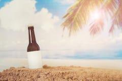 A garrafa vazia de Logo Beer no lixa com fundo da praia fotos de stock