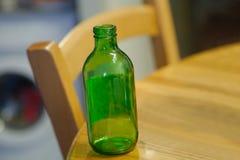 Garrafa vazia na tabela Fotos de Stock