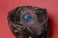 Garrafa vazia plástica em um saco preto no recipiente no fundo vermelho Conceito da polui??o ambiental pelo lixo pl?stico imagem de stock royalty free