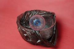 Garrafa vazia pl?stica em um saco preto no recipiente no fundo vermelho Conceito da polui??o ambiental pelo lixo pl?stico foto de stock