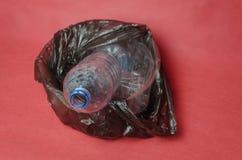 Garrafa vazia pl?stica em um saco preto no recipiente no fundo vermelho Conceito da polui??o ambiental pelo lixo pl?stico imagens de stock