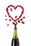 Garrafa vermelha dada forma coração do champanhe das pétalas cor-de-rosa foto de stock