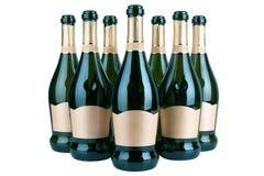 Garrafas abertas do champanhe ou do vinho espumante com etiqueta dourada em diversas fileiras no fundo branco isolado perto acima imagem de stock