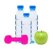 Garrafas azuis com água, dumbell e a maçã verde Foto de Stock