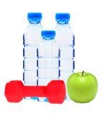 Garrafas azuis com água, dumbell vermelho e a maçã verde isolados Fotografia de Stock Royalty Free