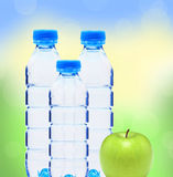 Garrafas azuis com água e a maçã verde sobre a natureza borrada Imagem de Stock Royalty Free