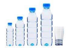 Garrafas azuis com água e os vidros isolados no branco Fotografia de Stock Royalty Free