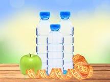 Garrafas azuis com água, medida da fita e a maçã verde em de madeira Imagem de Stock