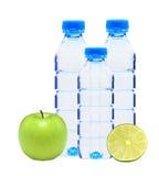 Garrafas azuis com água, o cal e a maçã verde isolados no branco Fotografia de Stock