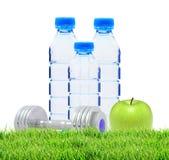 Garrafas azuis com água, pesos cromados e a maçã verde Fotografia de Stock