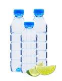 Garrafas azuis com as fatias da água e do cal isoladas no branco Fotos de Stock