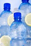 Garrafas azuis da água no gelo Fotografia de Stock