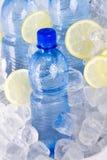 Garrafas azuis da água no gelo Imagens de Stock Royalty Free