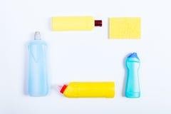 Garrafas azuis e amarelas do detergente e das esponjas em uma parte traseira do branco Foto de Stock Royalty Free