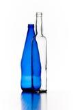 Garrafas azuis e transparentes do vidro isoladas no backgrou branco Imagens de Stock Royalty Free