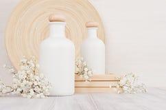 Garrafas brancas vazias dos cosméticos com as flores pequenas na placa de madeira branca, espaço da cópia, zombaria acima Fotografia de Stock