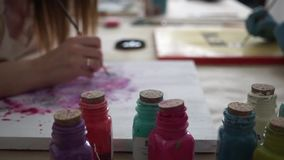 Garrafas coloridos da pintura O artista da menina tira letras na placa da cor vídeos de arquivo