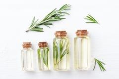 Garrafas com óleo aromático dos alecrins no fundo de madeira branco imagem de stock royalty free