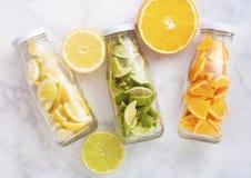 Garrafas com as laranjas com fatias dos cais e dos limões Fotografia de Stock