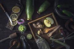 Garrafas com batido verde e os ingredientes diferentes na opinião superior da bandeja de madeira Fotografia de Stock Royalty Free