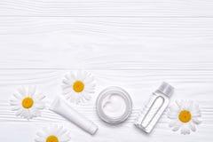 Garrafas com cosméticos e flores da margarida no fundo de madeira branco imagem de stock royalty free