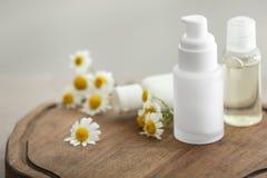 Garrafas com produtos cosméticos e as flores frescas da camomila fotografia de stock royalty free