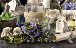 Garrafas da bruxa com ervas e rolo Imagens de Stock Royalty Free