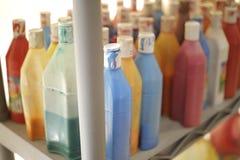 Garrafas da pintura líquida em uma prateleira Foto de Stock