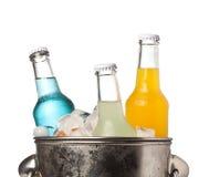 Garrafas da soda e do gelo em uma cubeta Fotografia de Stock Royalty Free