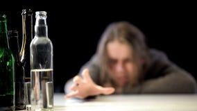 Garrafas da tabela da vodca, do vinho e da cerveja, mulher viciado que estica o fundo da mão imagem de stock royalty free